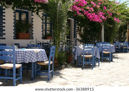 Typical greek taverna with tables outside in the yard - stock photo