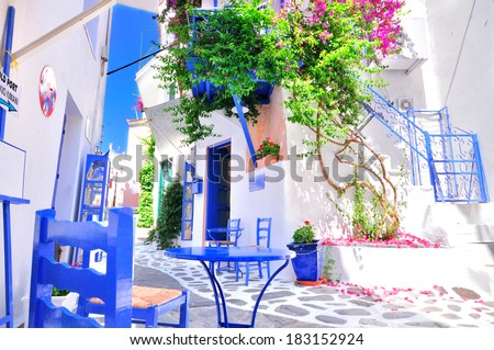 Typical greek traditional village in summer with white walls, blue furniture and colorful bougainvilla, Skiathos Island, Greece, Europe - stock photo