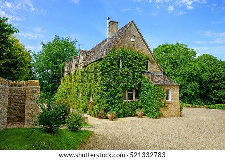 Typical Green Ivy Covered Cotswold Cottage In The Cotswolds England UK