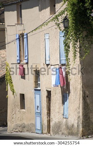 typical house in south France with blue shutters and drying laundry outside the windows in the old mountain village of Cadenet, Provence, Luberon Massif - stock photo