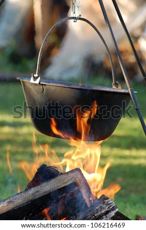 Typical Hungarian Guly�¡s (Soup) is jut cooking in Cauldron on Campfire