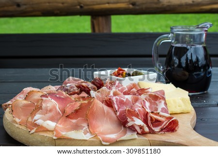 typical Italian appetizer with salami, cheese and pickles in a wooden cutting board - stock photo