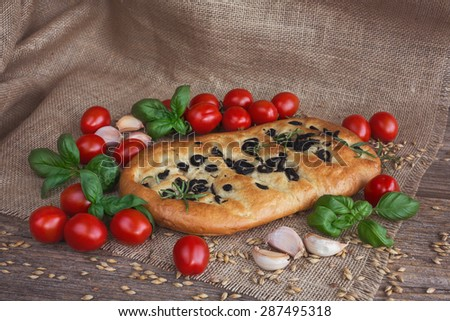 Typical Italian focaccia bread, cherry tomatoes, basil leaves, garlic. Toned - stock photo