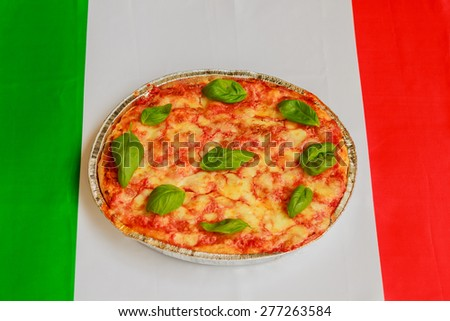 typical italian pizza  made of tomato,basil and mozzarella with the italian flag in the background - stock photo