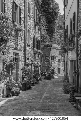 typical Italian street in a small provincial town of Tuscan, Italy, Europe . Black and white photography. - stock photo