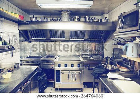 Typical kitchen of a restaurant shot in operation, toned image - stock photo