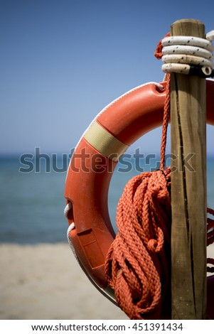Typical lifebuoy for a lifeguard to save people from drowning, put on the beach - stock photo