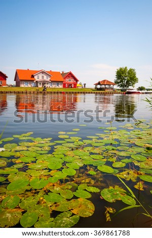 Typical lithuanian house by the lake in summer - stock photo