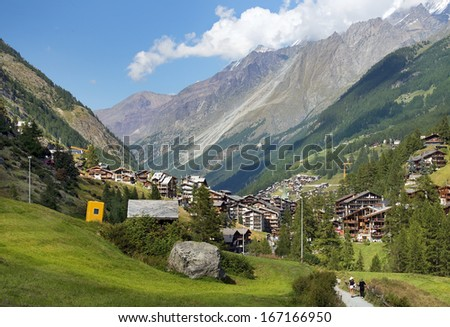 typical little resort town in the Swiss Alps with views of the mountain peaks - stock photo