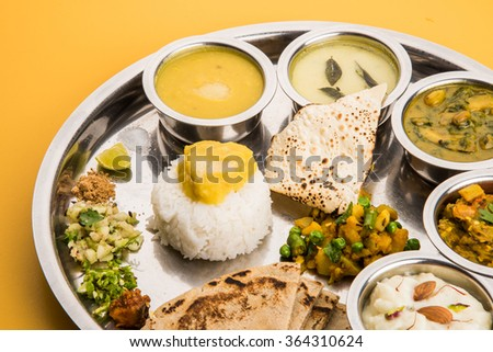 typical maharashtrian food served in a steal plate, marathi food includes kadhi and shrikhand, plain dal, spinach curry, aalu mutter, plain rice, papad, bhakri or bhakar or roti and variety of salad - stock photo