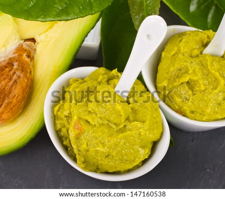 typical Mexican food - guacamole in white bowls with spoons on a black tray, decorated with green leaves isolated on white background - stock photo