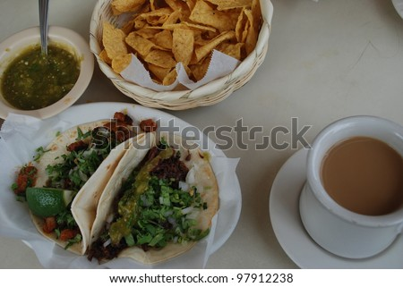 Typical Mexican food served at a South Austin Mexican restaurant includes taco al Pastor, taco de Barbacoa Coffee chips and hot salsa during SXSW 2012. - stock photo