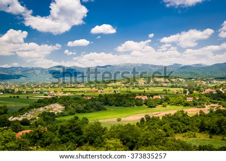 Typical Montenegrin rural landscape. Village houses in the fields, small river and mountain range on a background. Niksic, Montenegro.
