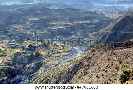 Typical mountain bird eye view  landscape. It is southern  American country -  Peru. Sacred Valley with the cultivated farmer fields is surrounded with high hills. On terraces poor farmers  grow corn.