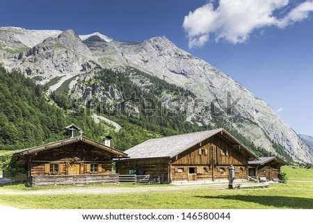 Typical mountain huts in the Austrian Alps at a place called Hinterriss, Eng on a sunny day with rocky mountains in the background - stock photo