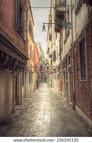 typical narrow alley in street of Venice (Venezia) at a rainy day, vintage style, Italy, Europe - stock photo