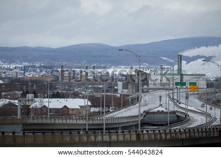Typical North America Expressway in winter on a cloudy day with a fuming factory on the background in Quebec City, QC, Canada