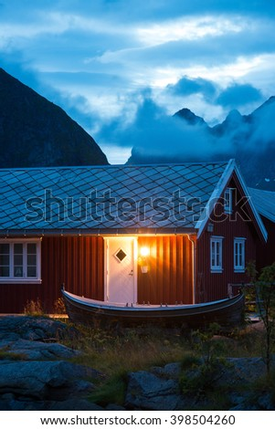 typical Norway red fishing hut with fishing wooden boat in the evening near great mountains  - stock photo