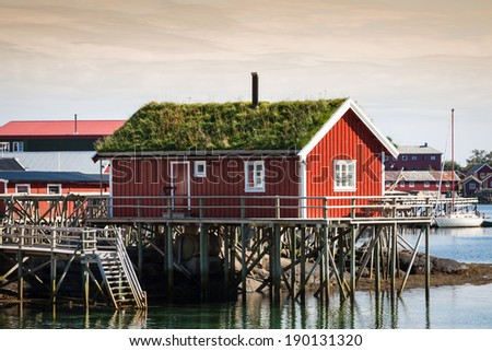 Typical Norwegian fishing village with traditional red rorbu huts, Reine, Lofoten Islands, Norway - stock photo