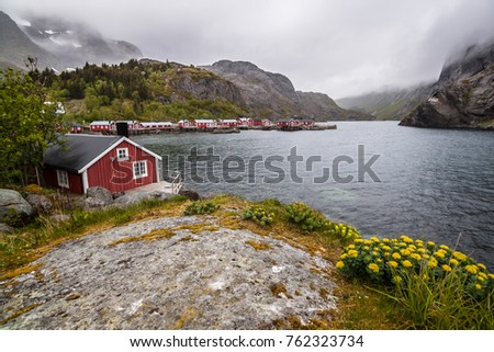 Typical norwegian red houses Rorbu in Lofoten village of Nusfjord. Classical fishermen village by the sea surrounded by high peaks of Lofoten. Blue sky with grey clouds make great nordic atmosphere.
