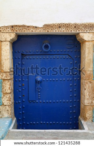 Typical, old, blue intricately carved, studded, Moroccan riad door and door-frame, Azemmour, El Jadida, Morocco. - stock photo