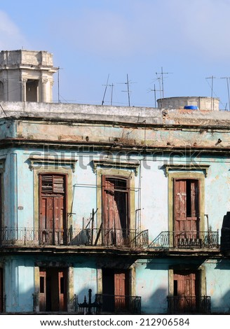 Typical old, broken-down balconies in need of repair, in Old Havana, Cuba. The blue paint on the masonry is typical of old buildings in this part of Havana. - stock photo