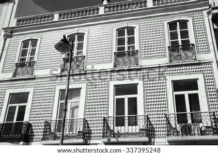 Typical old building in the centre of Lisbon (Portugal). Ceramic tiles (azulejos)  with rhombus pattern, balconies with forging railing and balustrade on the roof.  Aged photo. Black and white. - stock photo