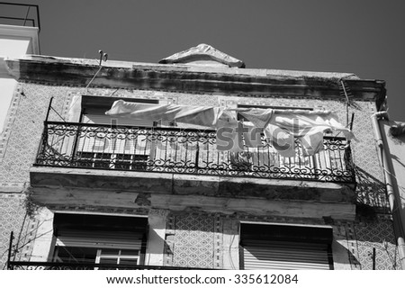 Typical old building in the centre of Lisbon (Portugal) with ceramic tiles (azulejos) and the linen and kitchen towels hanging to dry on the sun. Aged photo. Black and white. - stock photo
