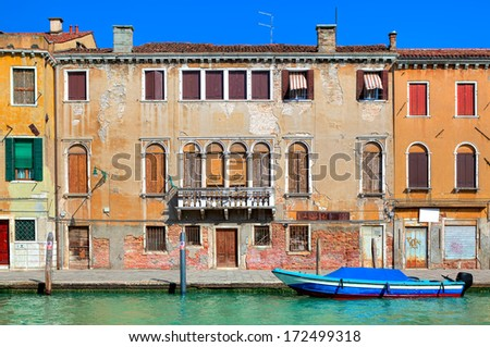 Typical old colorful brick house, wooden shutters on windows and small canal in Venice, Italy. - stock photo