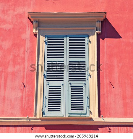 typical old grey french shutter window in red house of Nice, Cote d'azur, France. Square toned image  - stock photo