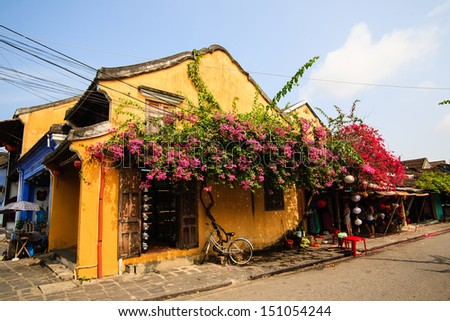 Typical old house with yellow wall, red paper flower and wooden doors at a corner in Hoi An Ancient Town, Quang Nam, Vietnam. Hoi An is recognized as a World Heritage Site by UNESCO. - stock photo
