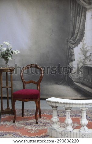 typical old photo studio with chair, table, flowers and a marble balustrade - stock photo