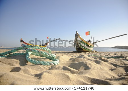 Typical old portuguese fishing boats with rope infront on the beach of Espinho, Portugal - stock photo