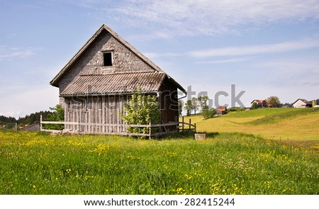 Typical old wooden shingle outhouse in Switzerland countryside on blooming spring meadow