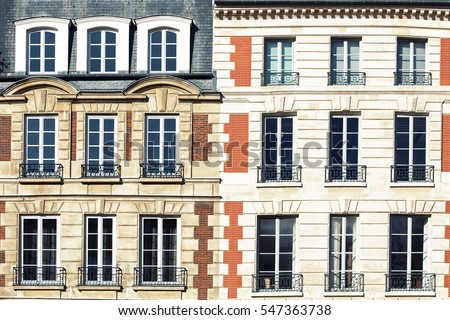 Typical Parisian architectural. The facade of a red brick building in Paris showing window details with wrought iron railings.