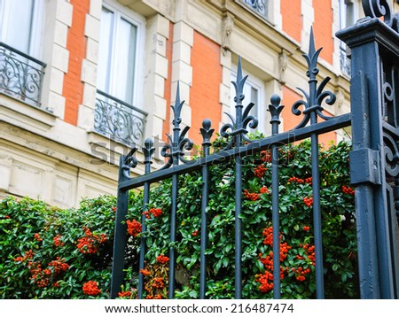 Typical Parisian building with forging gate and colorful firethorn bushes. Autumn in Paris. - stock photo