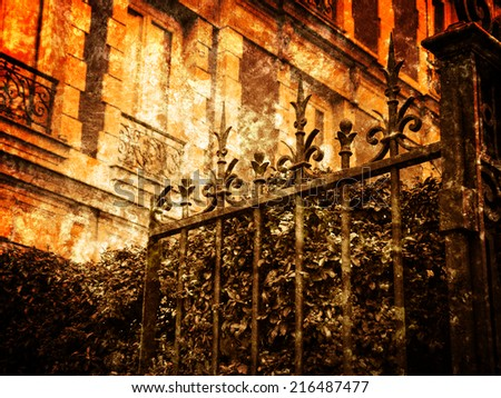 Typical Parisian building with forging gate and colorful firethorn bushes. Autumn in Paris. Retro aged photo with scratches. Ocher toned.
