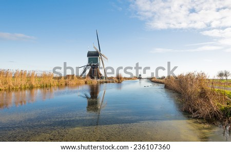 Typical polder landscape in the Netherlands with a row of two windmills reflected in the mirror smooth water surface. - stock photo