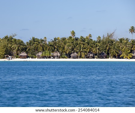 Typical Polynesian landscape - seacoast with palm trees and small houses  - stock photo