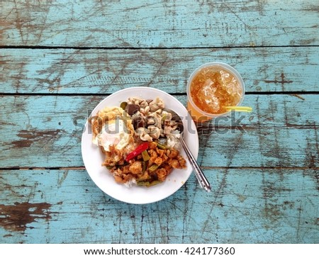 typical popular fast food THAI lunch menu everywhere, rice with fried chicken or pork with hot chili and basil leafs served with iced natural soft drink authentic shot on textured school canteen table - stock photo