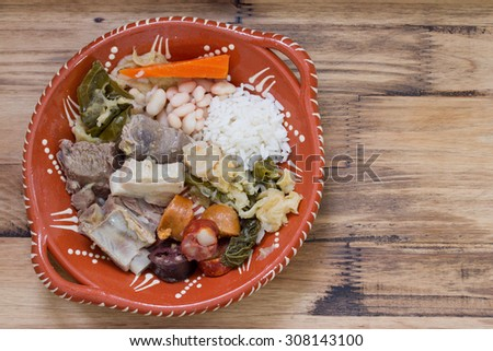 typical portuguese dish on ceramic plate on brown wooden background - stock photo