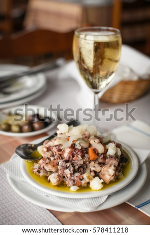 Typical Portuguese octopus salad with the glass of white wine as it served in Porto Covo, the western Alentejo coast of Portugal.