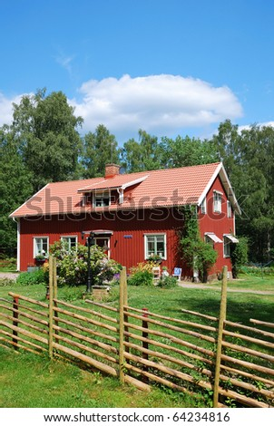 Typical red cottage is in the green yard overgrown with grass and flowers. In the background there are summer forest and the blue sky. The estate is enclosed with traditional wood fence. - stock photo