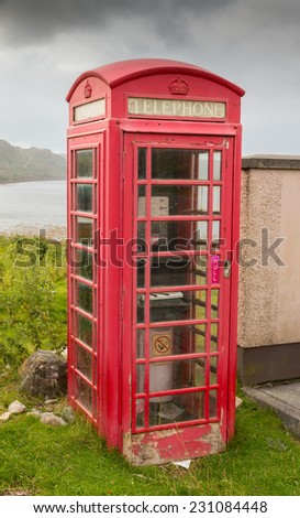 Typical red phone booth at the shore of Loch Inchard near Rhiconich village, Highlands, Scotland - stock photo