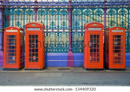 Typical red phone booths in a row on smithfields market or London Central Markets, the largest wholesale meat market in the UK and one of the largest of its kind in Europe - stock photo