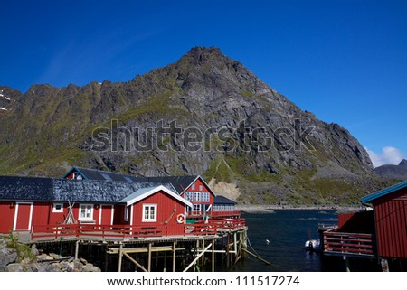 Typical red rorbu fishing huts by fjord on Lofoten islands in Norway - stock photo