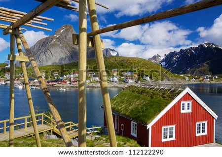 Typical red rorbu hut with sod roof in town of Reine on Lofoten islands in Norway - stock photo