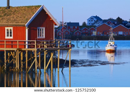 Typical red rorbu hut with sod roof lit by midnight sun in town of Reine on Lofoten islands in Norway - stock photo