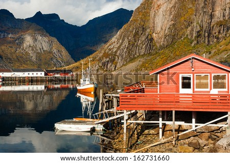 Typical red rorbu huts with sod roof in town of Reine on Lofoten islands in Norway  - stock photo