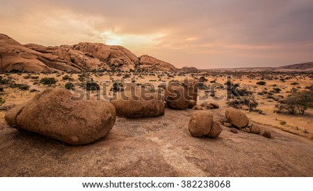 Typical round stones in the Namibian savanna at sunset - stock photo